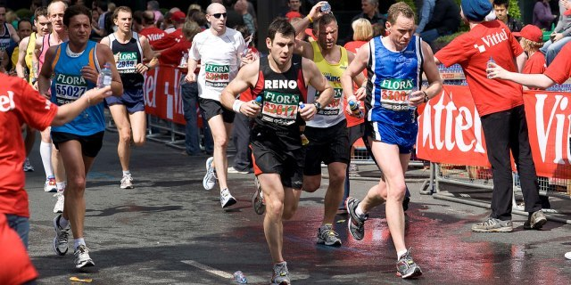 Runners at the London Marathon being offered water