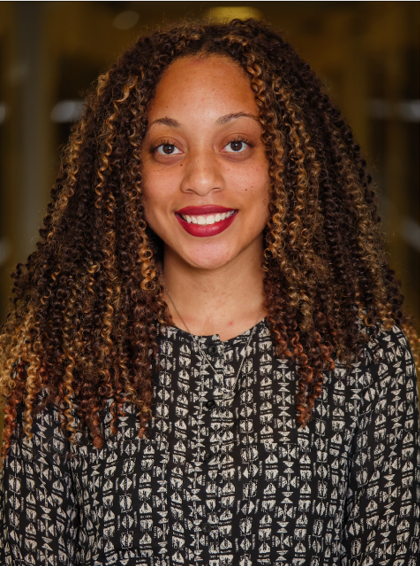 An image of Briana Brown, the Programs & Operations Coordinator for the National Science Policy Network. She is smiling and is wearing a black and white spotted shirt.