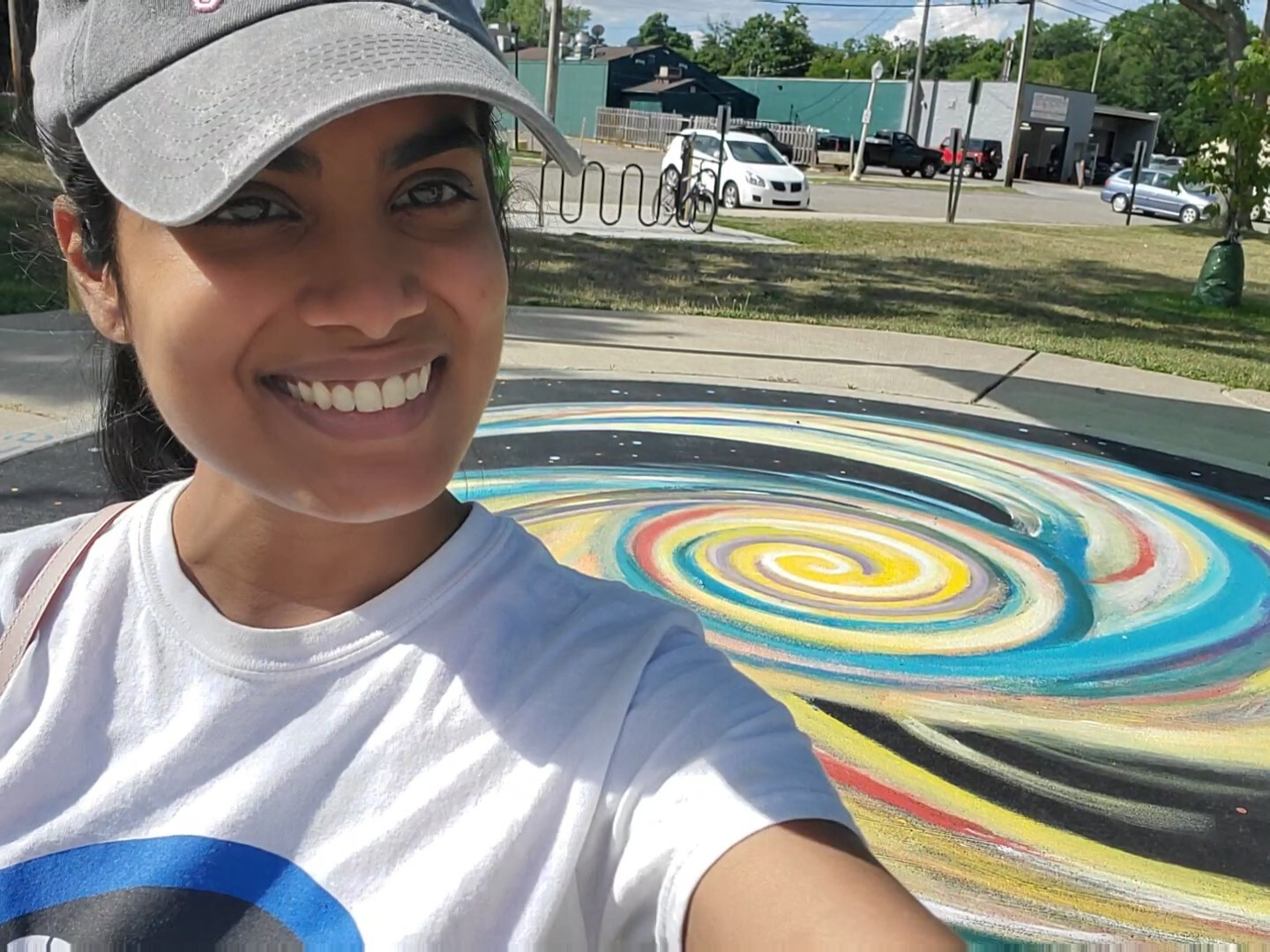 A photo of a person wearing a white T-shirt and a baseball cap. In the background is a piece of science art on the ground, consisting of a series of colored swirl shapes.