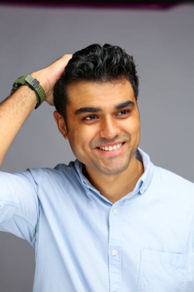 A photo of Pardeep Singh, wearing a light blue button up shirt and a watch. His right hand is on top of his head, and he is smiling as he looks into the distance.