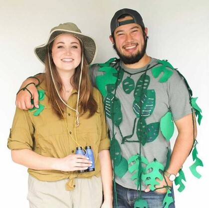 A photo of a man wearing fake leaves over his shirt and a woman wearing a straw hat.