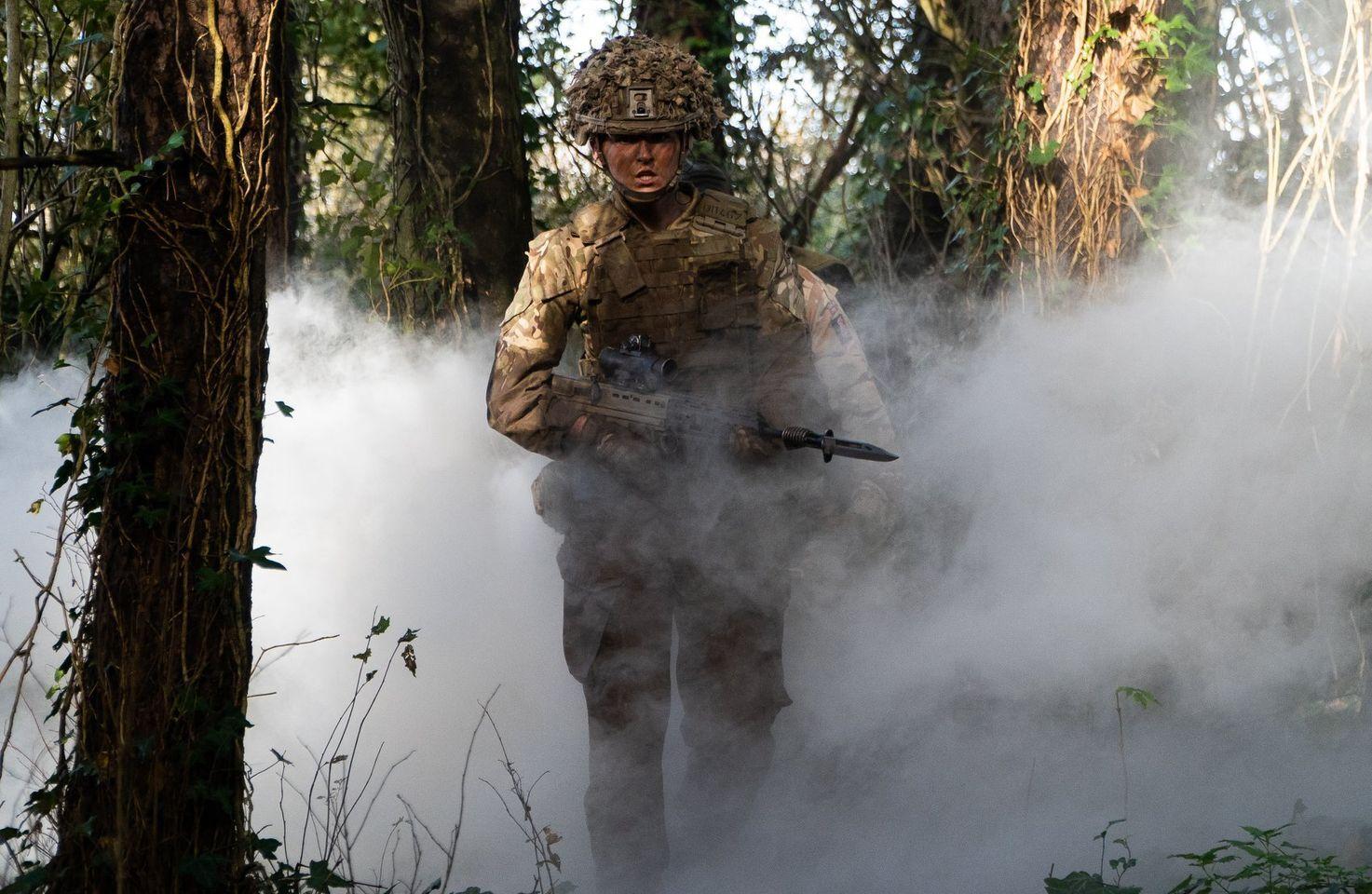 Female Rifleman walking through smoke filled woodland