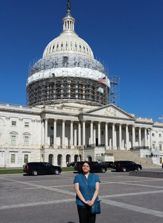 A photo of Amrita Banerjee standing in front of the Capitol Building in Washington, D.C. She is wearing a blue short sleeve shirt with black pants, and has her hands folded in front of her.