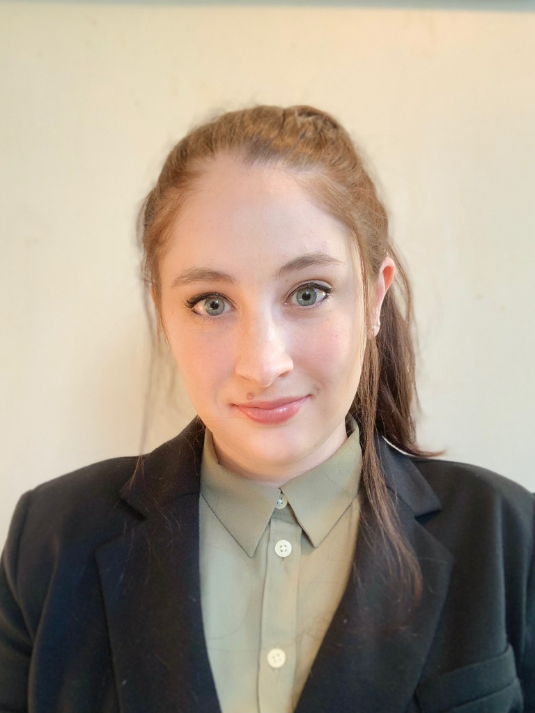 A photo of Caroline Schuerger wearing a light olive button-up shirt and a black jacket.