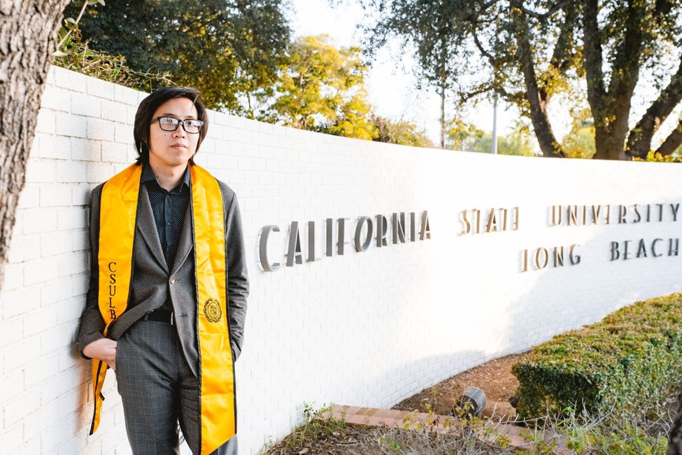 A photo of Richard Tran standing by a university sign wearing a graduation gown and yellow stole.